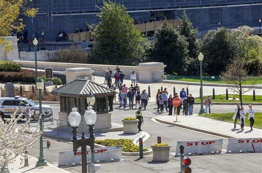 """Tourists and government workers are directed by police away from the Capitol at Constitution Ave. and Delaware Ave. in Washington, Monday, March 28, 2016. A gunman was taken into custody after firing shots in the U.S. Capitol complex. Capitol officials said, and visitors and staff were shut in their offices and told to """"shelter in place."""" (AP Photo/J. Scott Applewhite) Photo: J. Scott Applewhite"""