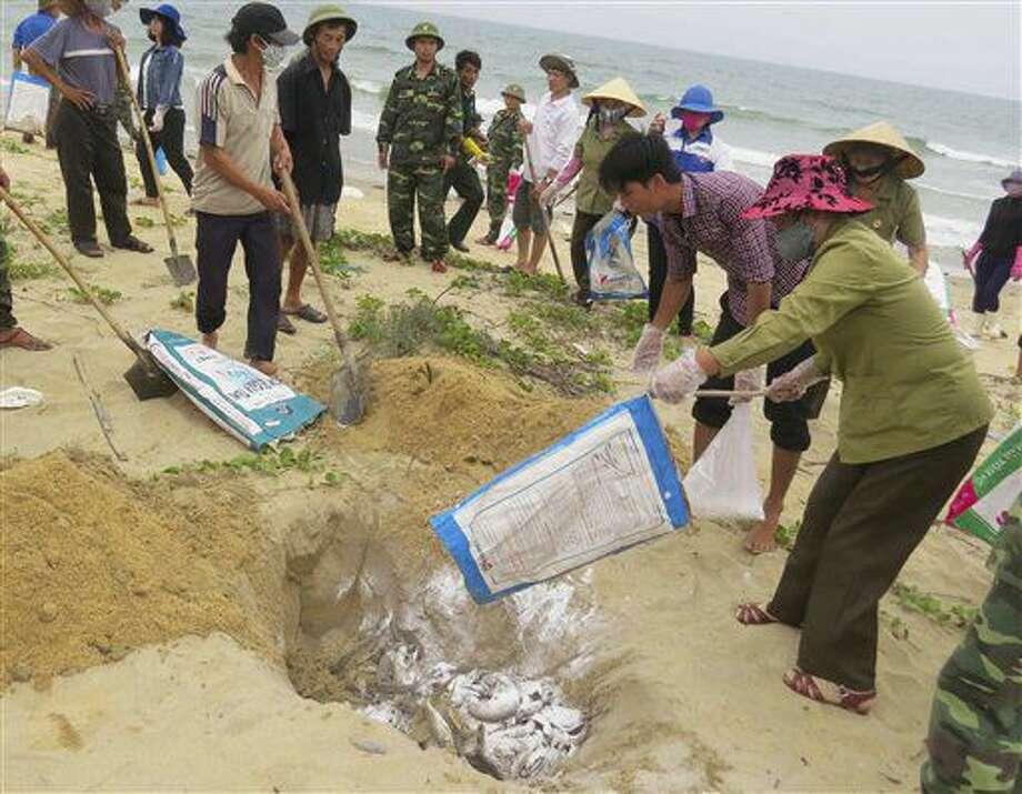 En esta imagen del 28 de abril de 2016, vecinos enterrando peces muertos en una playa en Quang Binh, Vietnam. El gobierno vietnamita declaró el jueves 30 de junio de 2016 que la firma taiwanesa Formosa Ha Tinh Steel Corp. era responsable de la muerte de unas 70 toneladas de peces que comenzaron a quedar en las playas a lo largo de más de 200 kilómetros (125 millas) de costa en cuatro provincias a principios de abril. (Vo Thi Dung/VNA via AP) Photo: Vo Thi Dung