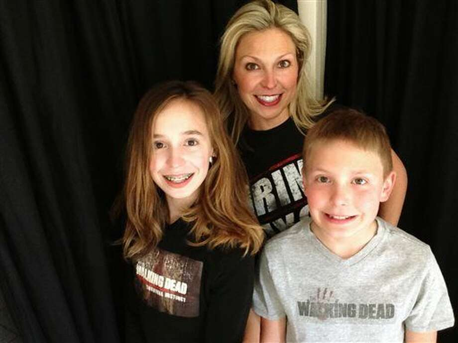 "Ericka Calcagno, center, is shown with her daughter, Gina Binder, 12, left, and son, Jean-Luc Binder, 9, wearing T-shirts from, ""The Walking Dead,"" at their home in Farmington Hills, Mich. Calcagno says her husband first introduced her to the series and her kids were intrigued by their conversations about it. And now they all watch the popular zombie show as a family. Photo: Ericka Calcagno Via AP"