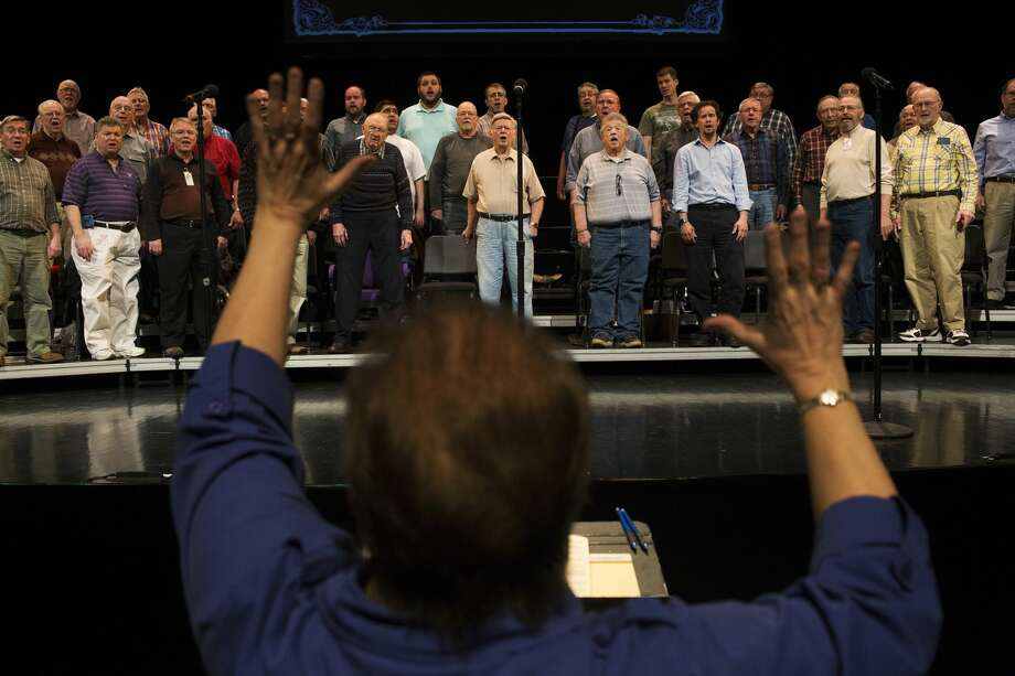 """Grace Marra, director, instructs the singers of the Men of Music from the music pit during a rehearsal at the Midland Center for the Arts auditorium on Tuesday. The all mens singing group is celebrating its 80th anniversary with their spring show, """"80 years: from Vaudeville to Broadway."""" Photo: Theophil Syslo 