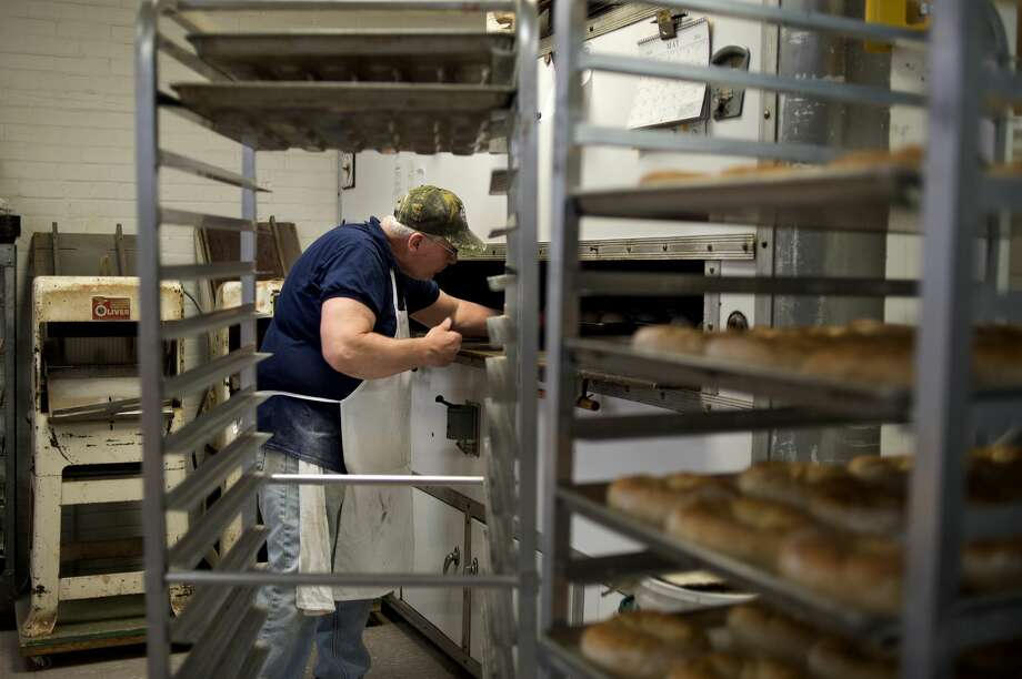 Matt Hamilton of Midland pulls out freshly baked bread from the oven at Cops & Doughnuts in Clare. Photo: Brittney Lohmiller | Midland Daily News