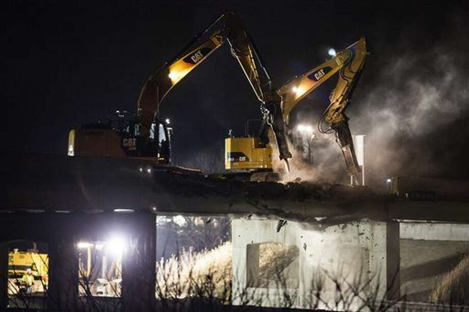 Demolition crews work to remove a damaged overpass on 8 Mile Road bridge over U.S. Highway 23 near Whitmore Lake, Mich., late Thursday, March 10, 2016 after a semi-truck hit the bridge earlier in the morning. (Allison Farrand/The Ann Arbor News via AP) Photo: Allison Farrand