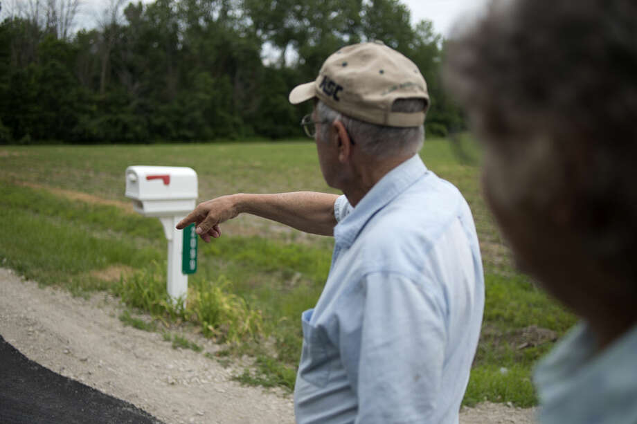 Chuck Finney of Midland points to where he and his wife, Judy Finney, saw a bear walk out from the tree line on Thayer Road in Ingersoll Township Wednesday morning. Photo: Brittney Lohmiller | Midland Daily News