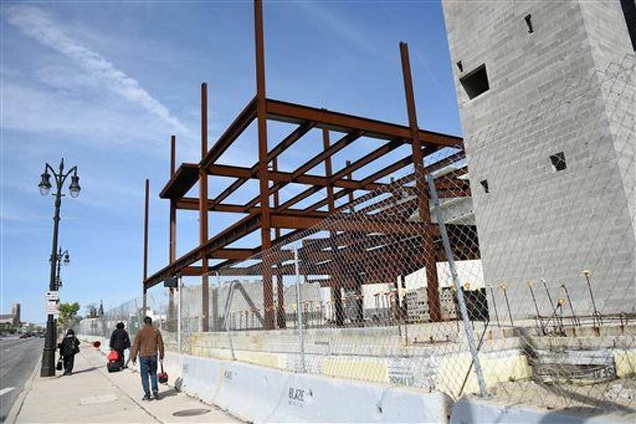 People pass the site of a suspended jail project in Detroit, Mich., Wednesday, April 27, 2016. Major League Soccer is eyeing the site as a possible home for a new soccer team in Detroit, part of a massive downtown development that would be built in the same area where the Tigers, Lions and Red Wings play. (Tanya Moutzalias /The Ann Arbor News - MLive.com Detroit via AP) Photo: Tanya Moutzalias