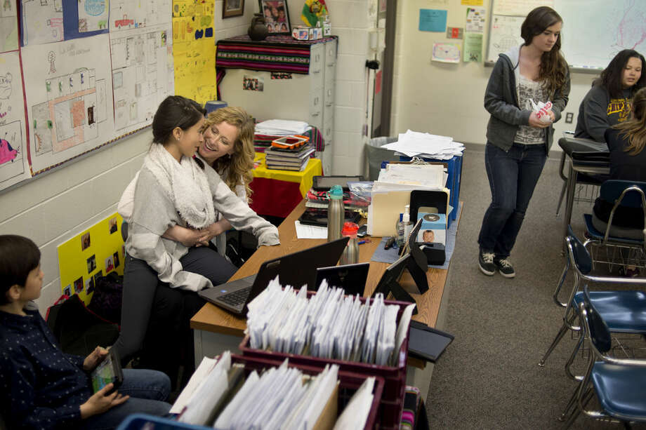 "Midland High School Spanish teacher Heather Aviles jokes with her daughter, Chloe Aviles, 10, as her son, Gabriel Aviles, 8, looks on while waiting for the Spanish 3 students to get seated on Thursday as part of ""Take Our Daughters and Sons to Work Day."" Photo: Brittney Lohmiller 