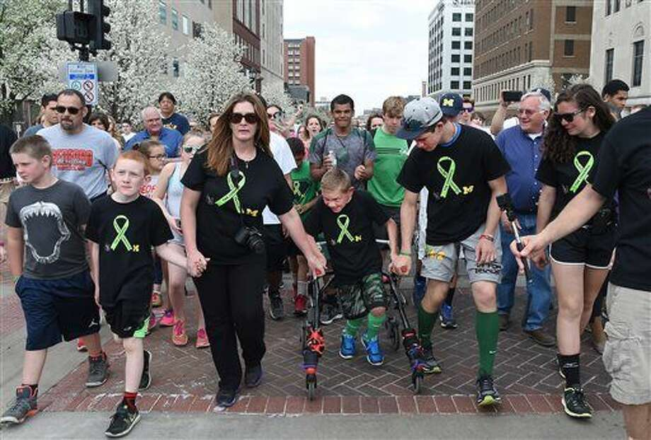 Braden Gandee, 9, center, of Temperance, who has Cerebral Palsy, walks the last half mile down E. Michigan Ave. at the end of Cerebral Palsy Swagger walk in front of the state Capitol in Lansing, Mich., Monday, April 25, 2016. He was with his mother Danielle Gandee (left), brother Hunter Gandee, 16, (right) who carried Braden 110.5 miles to bring awareness to Cerebral Palsy. The other family members were his brother Kellen Gandee, 8, (far left), and sister Kerragan, 15, (far right). (Tom Hawley/The Monroe News via AP) Photo: TOM HAWLEY