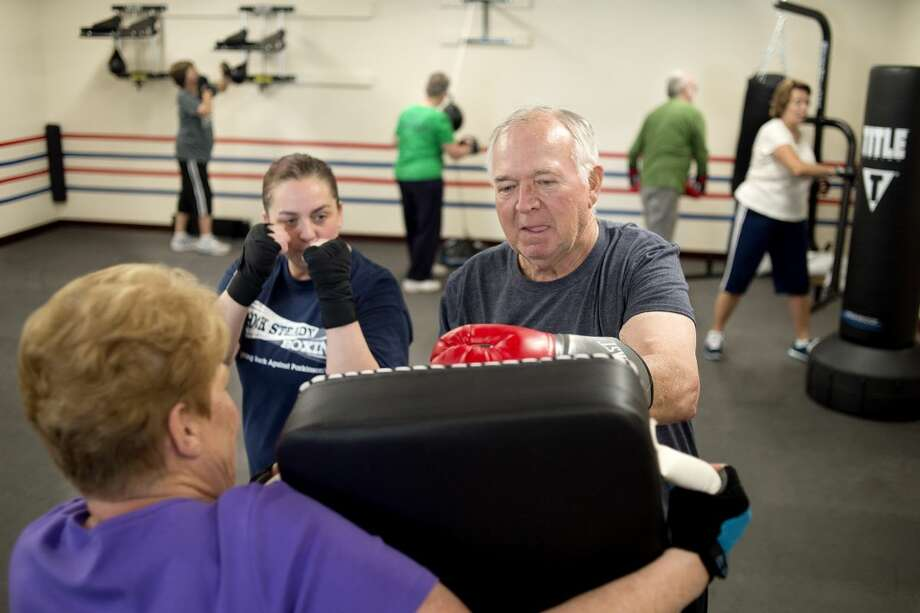 "Carole Wolf of Midland holds a punch pad while Rock Steady Boxing owner and head coach Stacey Hannah, left, works with Tom Billingsley of Sanford on Wednesday. Starting May 2, the boxing gym will be solely open for Parkinson patients. ""Being a massage therapist for Parkinson patients it was disheartening to only be able to make them comfortable for a day or two,"" Hannah said. ""I want to help them hug their grandchildren or go grocery shopping. This is something that can help."" Photo: Brittney Lohmiller 
