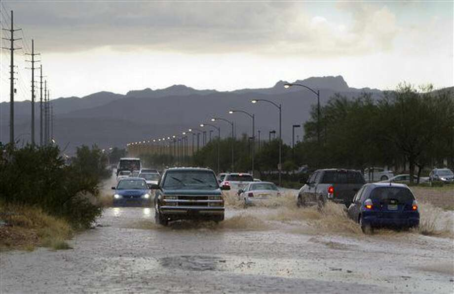 Cars and trucks drive through run-off on Sunset Road near Jones Boulevard after a thunderstorm dropped heavy rain and hail in the Las Vegas valley Thursday, June 30, 2016. The National Weather Service issued a flash flood warning after intense thunderstorms in mountain and canyon areas near Mount Charleston northwest of Las Vegas. (Steve Marcus/Las Vegas Sun via AP) Photo: Steve Marcus
