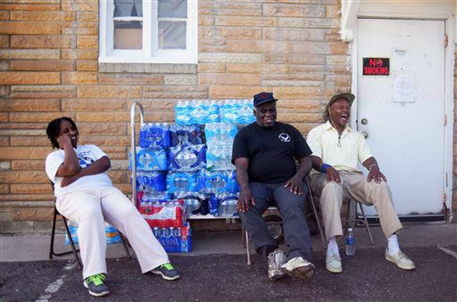"""Stephanie Smith, left, Jimmie Thompson, center, and Otis Ross, right, share a laugh in-between residents coming to get water at Prince of Peace Baptist Church Wednesday, June 22, 2016 in northwest Flint. Every Monday, Wednesday and Friday the church gives out water for free from 10 a.m. to 2 p.m. """"My brother lives in Atlanta. I try to tell him he doesn't realize how bad the water crisis is here,"""" Ross said. """"You can't imagine it until you get here."""" (Mark Felix/The Flint Journal-MLive.com via AP) LOCAL TELEVISION OUT; LOCAL INTERNET OUT; MANDATORY CREDIT"""