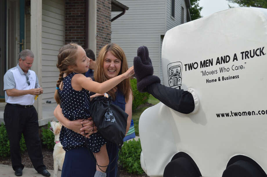 Kara Mohr and daughter, Jillian, meet Truckie, the Two Men and a Truck mascot. Photo: Photo Provided