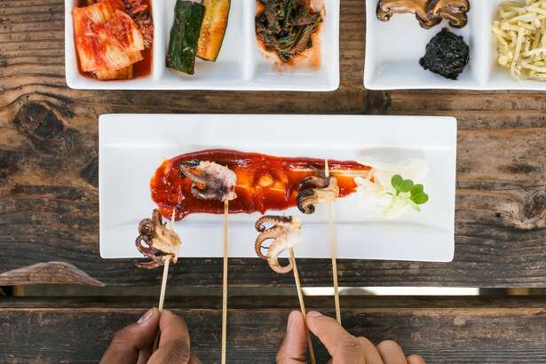 Saqib Keval and Jocelyn Jackson grab for the Octopus skewers, a special dish served at FuseBOX.