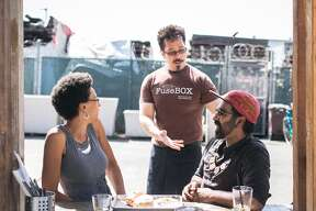Chef and co-owner, Sunhui Chang checks the quality of food served to Jocelyn Jackson and Saqib Keval at FuseBOX in Oakland.