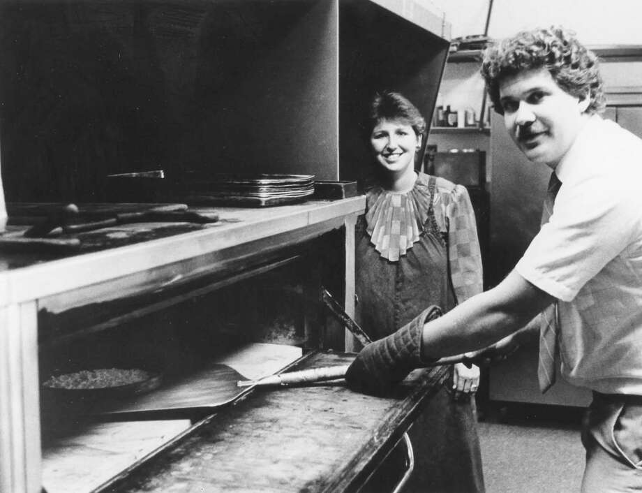 Gina Loose watches as her husband, Rick, removes pizza from one of their new ovens.