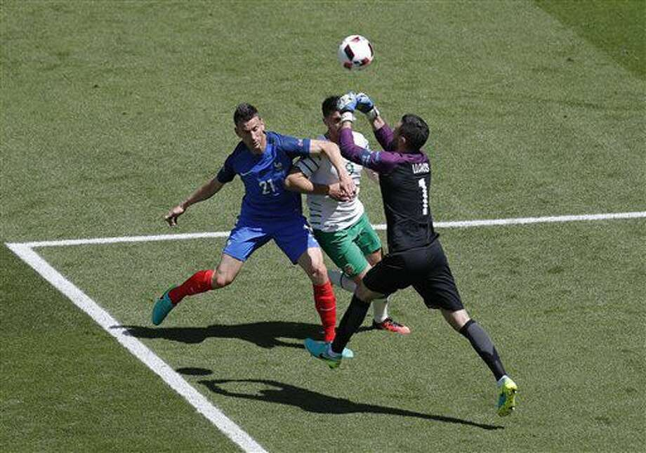 France goalkeeper Hugo Lloris, right, clears a ball followed by Ireland's Shane Long, center and France's Laurent Koscielny during the Euro 2016 round of 16 soccer match between France and Ireland, at the Grand Stade in Decines-Charpieu, near Lyon, France, Sunday, June 26, 2016. (AP Photo/Michael Sohn) Photo: Michael Sohn