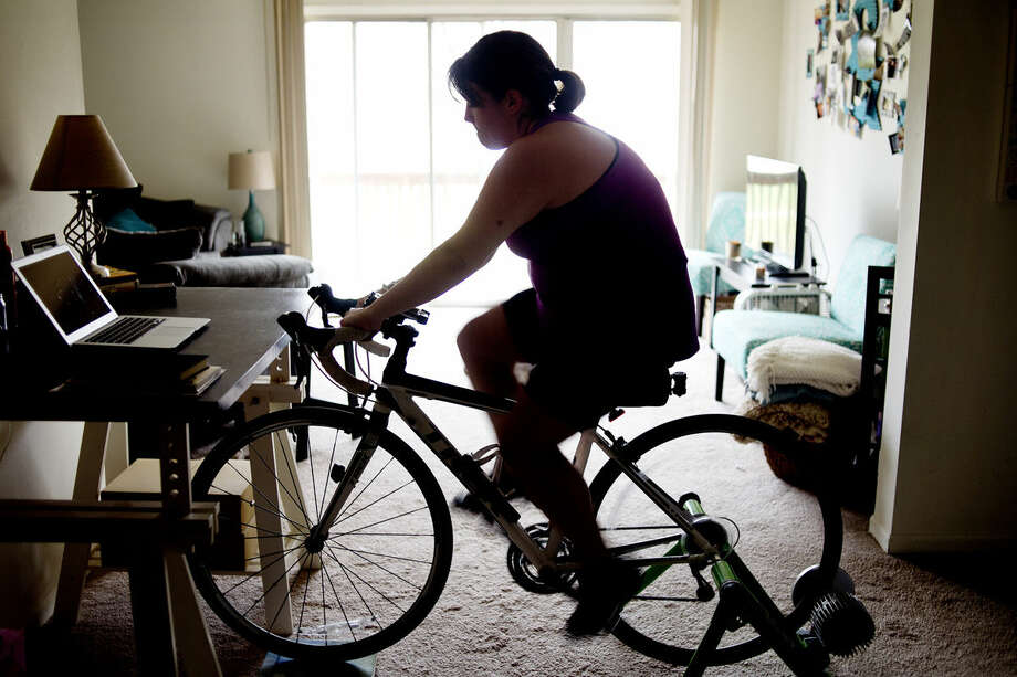 Caitlin Lambert of Midland rides her bike inside her apartment as part of the training for her upcoming Across America Tour. On June 2, she will begin biking from Los Angeles and complete the tour on July 11 at Jacksonville, Fla., traveling approximately 2,700 miles. Photo: Brittney Lohmiller | Midland Daily News
