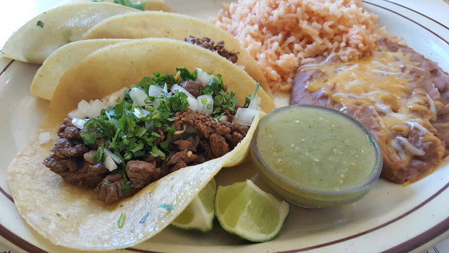 Elvira's Asada Taco plate comes loaded with three tacos in corn meal shells. Cilantro and diced onions come on the tacos, along with a side of salsa verde sauce and fresh pieces of lime. Mexican rice and refried beans round out the meal nicely. Photo: Matthew Woods