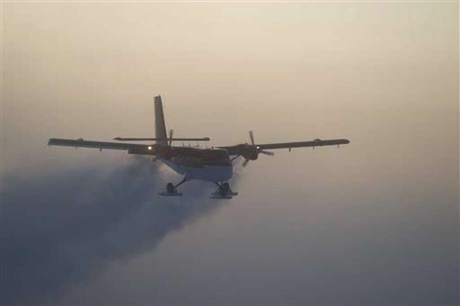 In this 2003 photo, provided by the National Science Foundation, a Twin Otter flies out of the South Pole on a previous medical flight. A Twin Otter airplane left a British base in Antarctica Tuesday, June 21, 2016, for the 1,500-mile trip to evacuate a sick person from the U.S. station. Athena Dinar, spokeswoman for the British Antarctic Survey, said one of two twin otter planes began the trip Tuesday, while the other is still at the Rothera station on the Antarctic Peninsula just in case. (Jason Medley, National Science Foundation via AP)