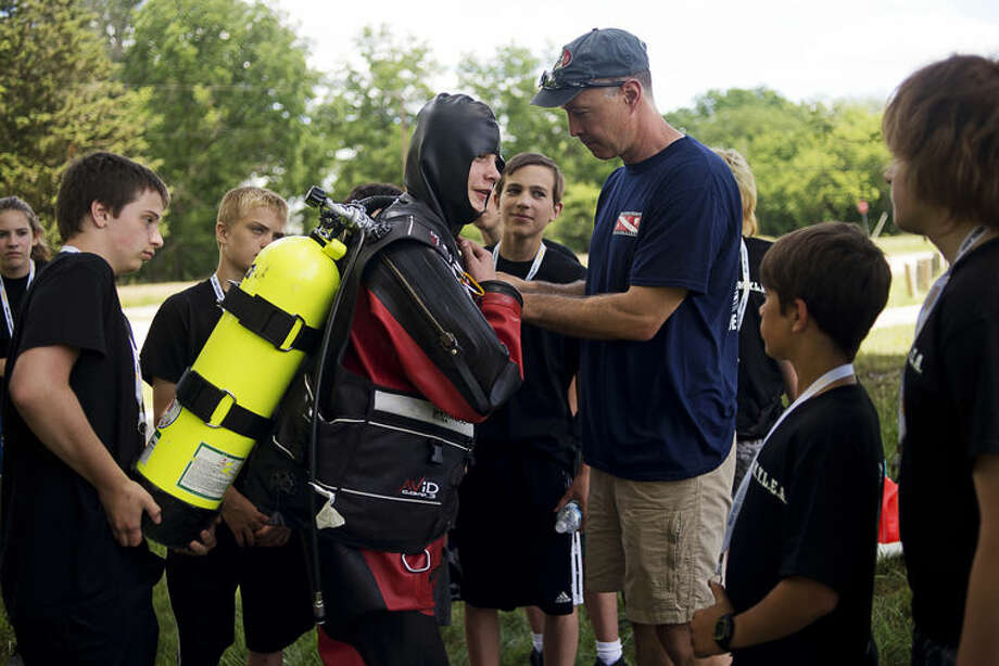 Midland Youth Law Enforcement Academy participant David Burlingame, 15, left, holds onto the oxygen tank as fellow participant Kyle Leigeb, 13, center, is assisted by Midland County Dive Team coordinator Tom Anderson, right, while trying on a cold water exposure suit on Tuesday at St. Charles Park. The academy is hosted by the Midland Police Department and the Midland County Sheriff's Office and is open to those between the ages of 13 and 15 who have an interest in pursuing a career in law enforcement or who just want to learn more about police work. Photo: Erin Kirkland | Midland Daily News