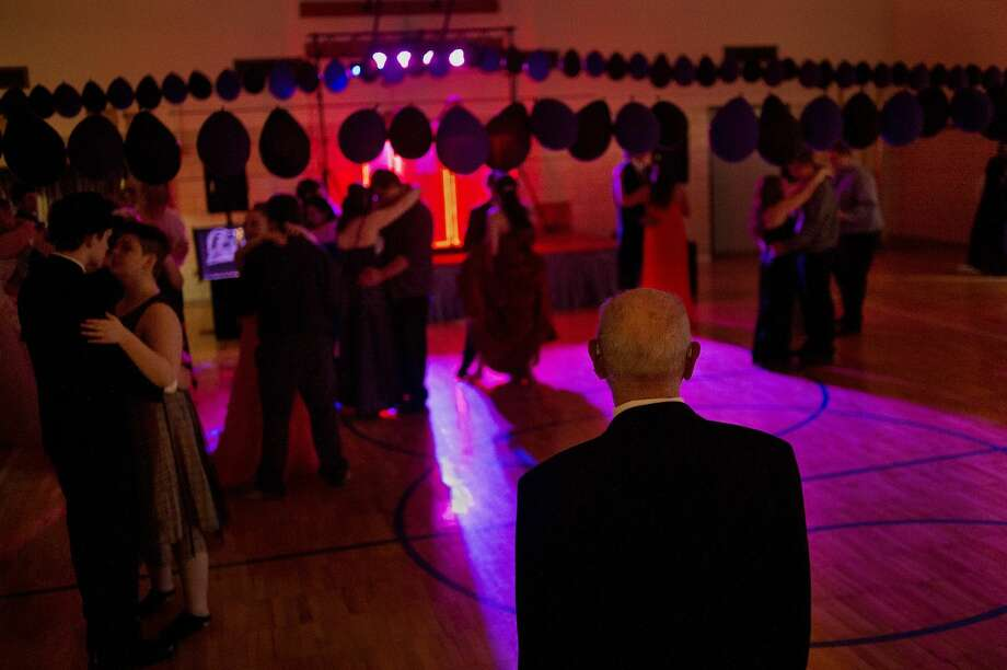 """Larry Lage, 90, of Midland, watches couples dance to Ed Sheeran's """"Thinking out loud"""" inside Windover High School's gym during the school's prom on Friday evening. """"It's fun seeing all the kids dressed up,"""" Lage said. After retiring from teaching Lage spends time volunteering at Windover. Photo: Brittney Lohmiller 