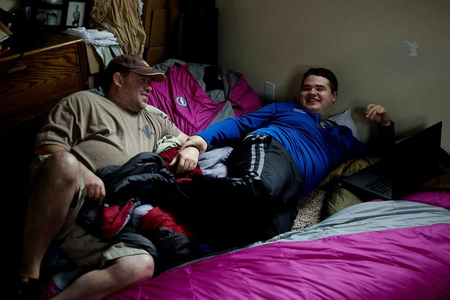 Dennis Mashue, left, smiles at his son, Tucker Mashue, 17, as the pair lounges on their sleeping bags on Friday at their Midland home. Dennis and Tucker are packing up their belongings, selling what doesn't fit in their van and trekking across the country on a months-long outdoor adventure. The pair will make stops in several cities to talk about their autism-centered microbusiness known as Tuck's Tooques. Photo: Erin Kirkland | Midland Daily News