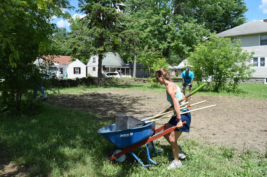 Midland resident Rebecca Faust loads up a wheelbarrow full of tools used to prepare a plot of land for a community garden on Roberts Street in Saginaw during One Week, One Street. Photo: Jessica Haynes | Jhaynes@mdn.net