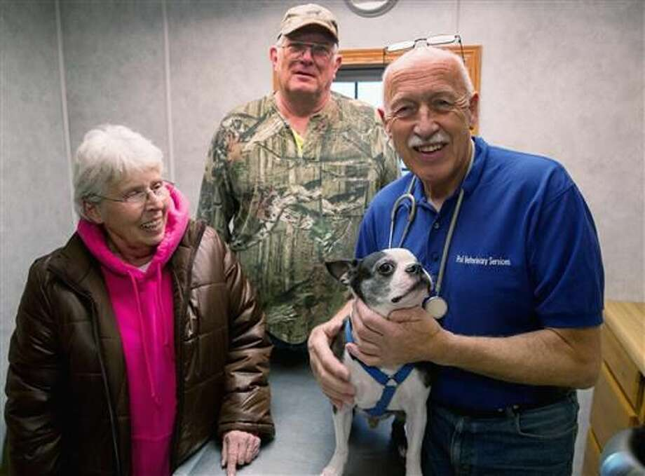 """In this March 2015 photo provided by Pol Veterinary Services, veterinarian Jan Pol, right, poses with Mr. Pigglesworth and the dog's owners owners Loyd and Mable Frisbie at his clinic near Mount Pleasant, Mich. An appeals court on Friday, June 24, 2016, cleared Pol of misconduct when he saved the dog's life in 2011. Pol has a reality TV show on Nat Geo Wild called """"The Incredible Dr. Pol."""" (E. Michael Stankevich/Pol Veterinary Services via AP)"""