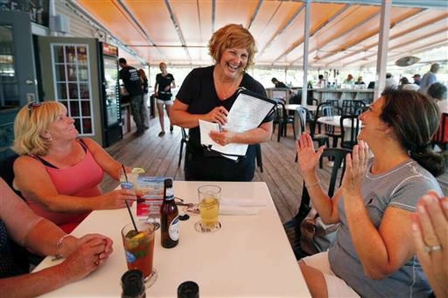 Ann LePage chats with diners after taking their order at McSeagull's restaurant, Thursday, June 23, 2016, in Boothbay Harbor. The wife of America's lowest paid governor has taken on a summer waitressing job near her and husband's Boothbay home, and she's saving up for a car. (AP Photo/Robert F. Bukaty)Summary