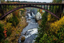 """NEW YORK: AUSABLE CHASM BRIDGE Discovered in 1765 by a man named William Gilliland, the Ausable Chasm is sometimes referred to as """"The Grand Canyon of the Adirondacks."""" The remarkable vertical-walled canyon is made of 500-million-year-old rock and provides visitors with opportunities to hike, bike, raft, rock climb - or simply enjoy the magnificent view of the chasm and this stunning steel arch bridge."""