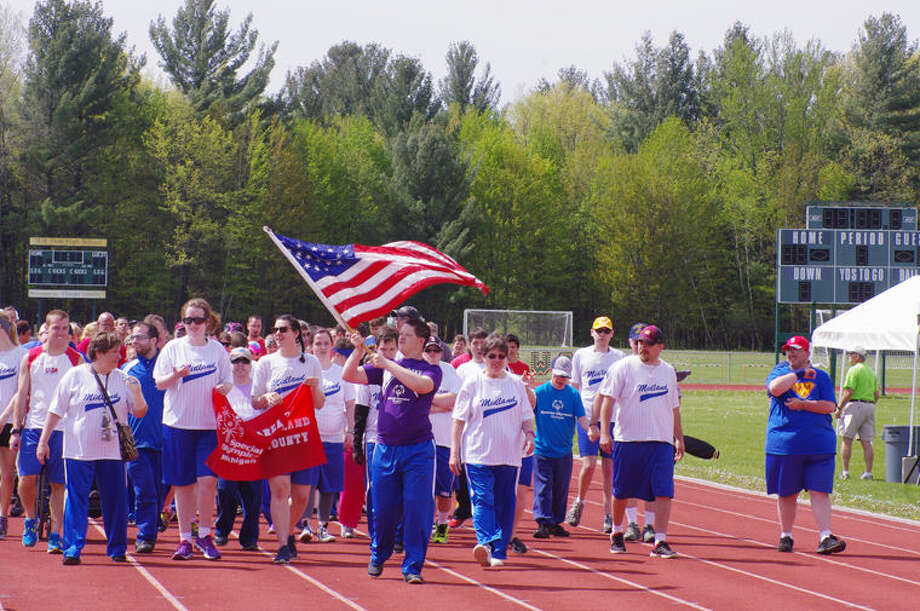 Midland area athlete Austin Shaver carries the American flag Saturday during the Special Olympics Summer Games opening ceremony's traditional procession around the H.H. Dow High School track. Photo: Photo Provided