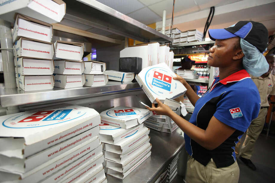 In this file photo, a worker prepares boxes at a Domino's pizza restaurant in Lagos, Nigeria. The New York attorney general has sued Domino's Pizza Inc., affiliates and three franchisees alleging they underpaid workers based on payroll reports generated by the parent company's computer system. Photo: AP Photo | Sunday Alamba, File