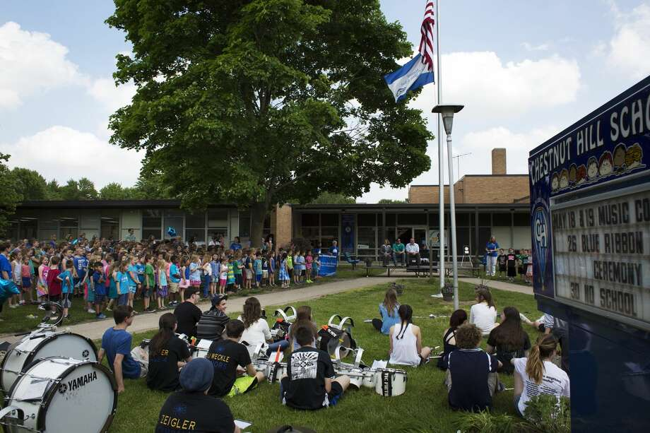 """Chestnut Hill Elementary School students stand during an award ceremony while the Midland High School pep band rest on the grass after performing the """"Star-Spangled Banner"""" at Chestnut Hill Elementary on Thursday. Chestnut Hill Elementary was recognized this year by the United States Department of Education as a Blue Ribbon School. The National Blue Ribbon Schools Program recognizes public and private elementary, middle, and high schools based on their overall academic excellence or their progress in closing achievement gaps among student subgroups. Every year the U. S. Department of Education seeks out and celebrates great American schools, schools demonstrating that all students can achieve to high levels. In its 32 year history, than 7,500 of schools across the country have been presented with this coveted award. National Blue Ribbon Schools represent the full diversity of American schools: public schools including charter schools, magnet/choice schools, Title I schools, and non-public schools including parochial and independent schools. They are urban, suburban, and rural, large and small, traditional and innovative, and serve students of every social, economic, and ethnic background.The National Blue Ribbon School award affirms the hard work of students, educators, families, and communities in creating safe and welcoming schools where students master challenging content. Photo: Theophil Syslo"""