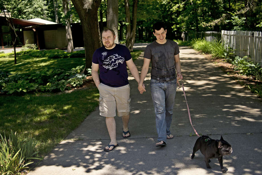 Brad Bidwell, left, and his husband Kyle Gordon, right, walk Greta on Friday outside their Larkin Township home. The couple was married in Canada in 2014, but were not recognized in the United States until the Supreme Court legalized gay marriage one year ago. The two, who are originally from the area, did not meet until attending school at Wayne State University. Photo: Erin Kirkland/Midland Daily News