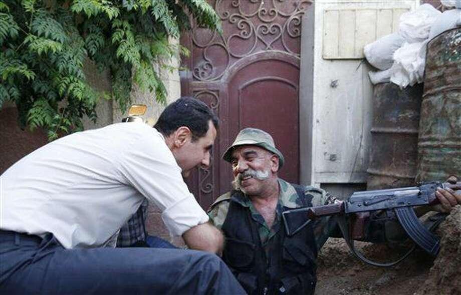 En esta fotografía difundida el domingo 26 de junio de 2016 por la agencia de noticias oficial de Siria, SANA, el presidente sirio, Bashar Assad, izquierda, habla con un soldado sirio durante su visita al frente en el suburbio de Damasco, Marj al-Sultan, en Siria. (SANA vía AP) Photo: Uncredited
