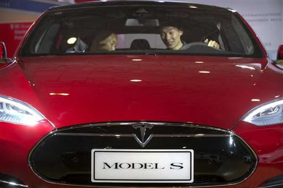 """In this Monday, April 25, 2016, file photo, a man sits behind the steering wheel of a Tesla Model S electric car on display at the Beijing International Automotive Exhibition in Beijing. Federal officials say the driver of a Tesla S sports car using the vehicle's """"autopilot"""" automated driving system has been killed in a collision with a truck, the first U.S. self-driving car fatality. The National Highway Traffic Safety Administration said preliminary reports indicate the crash occurred when a tractor-trailer made a left turn in front of the Tesla at a highway intersection. NHTSA said the Tesla driver died due to injuries sustained in the crash, which took place on May 7 in Williston, Fla. (AP Photo/Mark Schiefelbein, File)"""