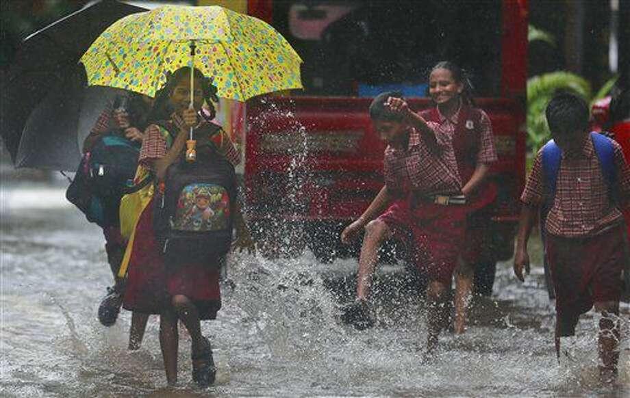 Una niña reacciona cuando la salpican de agua en una calle inundada en Mumbai, India, el martes 28 de junio de 2016. (AP Foto/Rafiq Maqbool) Photo: Rafiq Maqbool