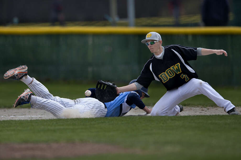 Petoskey's Joel Wilson slides into first base before Dow High's Jack Kucinski can tag him out during Saturday's tournament at Dow. Photo: Brittney Lohmiller/Midland Daily News