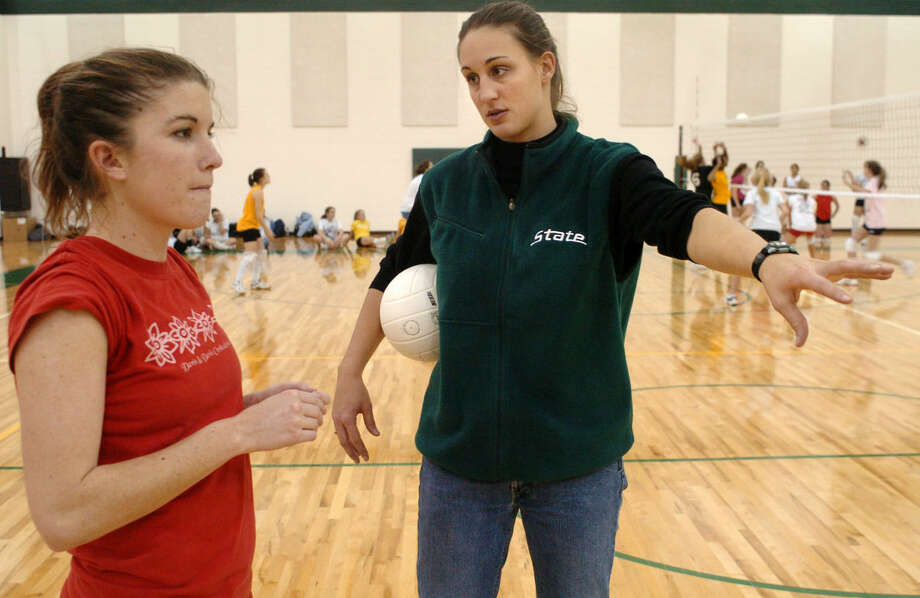 In this Daily News file photo from circa 2006, Erin Hartley (right) gives instruction to Dow High volleyball player Megan Justus. Hartley, a former Midland High and Michigan State volleyball standout, will be inducted into the Midland County Sports Hall of Fame on May 14.