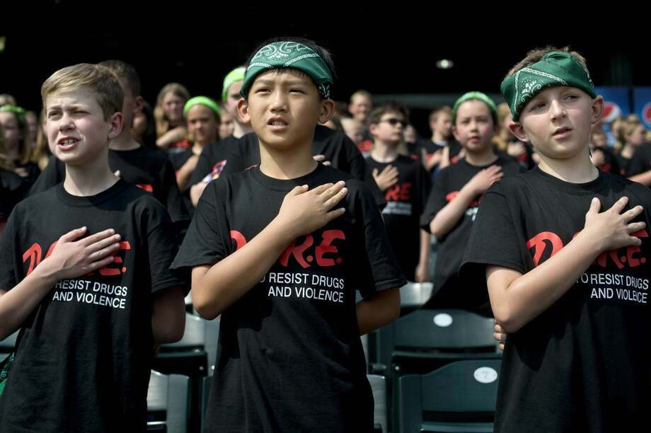 Woodcrest Elementary fifth-graders from left: Nick Yaroch, Daniel Shi and Jaydin Wood recite the pledge of alliance during D.A.R.E Day at Dow Diamond on Wednesday. The day is a reward for fifth grade students from schools across Midland County who completed the DARE program during the school year. Photo: Brittney Lohmiller/Midland Daily News