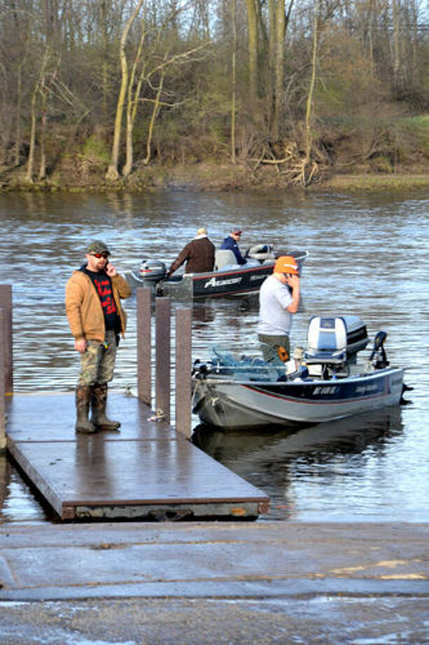 STEVE GRIFFIN | for the Daily News Walleye anglers at the Caldwell Launch Ramp on the Tittabawassee River Saturday morning use cell phones to connect with tow vehicles or fishing partners, or to report success or lack of it.