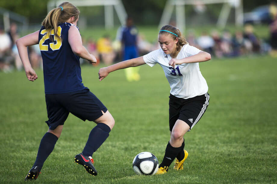 Calvary Baptist sophomore Savannah Wallace, right, dribbles past Rochester Hills Christian defender Sydney Yates, left, in the semifinals of the Michigan Association of Christian Schools girls' soccer tournament at the Midland Soccer Complex on Thursday. Wallace scored all three goals in the Kings' 3-0 win. Photo: Theophil Syslo