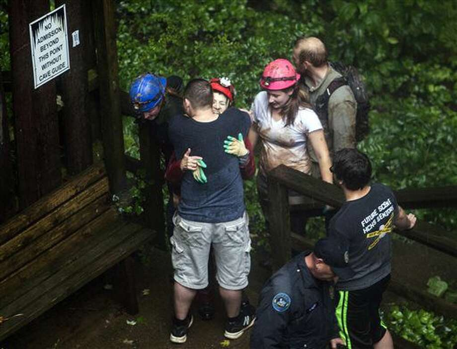 Tour guide Peggy Nims hugs a friend after she made it out of Hidden River Cave after officials said over a dozen people who were exploring the cave were trapped by rising water Thursday, May 26, 2016, in Horse Cave, Ky. The group waded through neck-deep water to get out, authorities said Thursday. (Austin Anthony/Daily News via AP) MANDATORY CREDIT Photo: Austin Anthony
