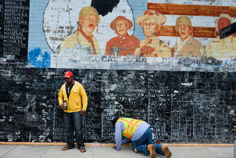 Former U.S. Marine Jon Scudder, left, watches as a Metropolitan Transit Authority worker prepares to cover a vandalized Vietnam War Memorial in the Venice area of Los Angeles on Monday, May 30, 2016. The Los Angeles memorial honoring prisoners and those missing in action during the Vietnam War has had to be covered with tarp on Memorial Day after authorities determined it was too badly damaged by graffiti to be quickly repaired. Photo: AP Photo/Richard Vogel
