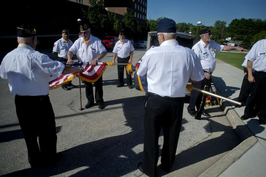 Members of the Sanford American Legion Post 443 put away flags following the completion of the wreath laying ceremony at the Midland County Veteran's Memorial during Memorial Day on Main Street. Photo: Brittney Lohmiller/Midland Daily News