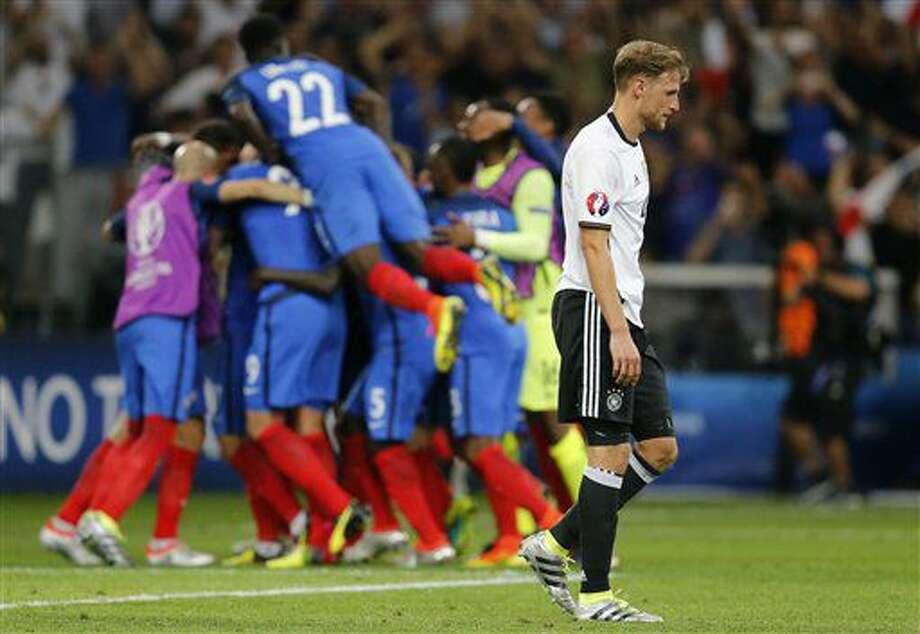 El jugador de Alemania, Benedikt Hoewedes, derecha, camina al frente de los jugadores de Francia que festejan un gol de Antoine Griezmann en las semifinales de la Eurocopa el jueves, 7 de julio de 2016, en Marsella, Francia. (AP Photo/Michael Probst) Photo: Michael Probst