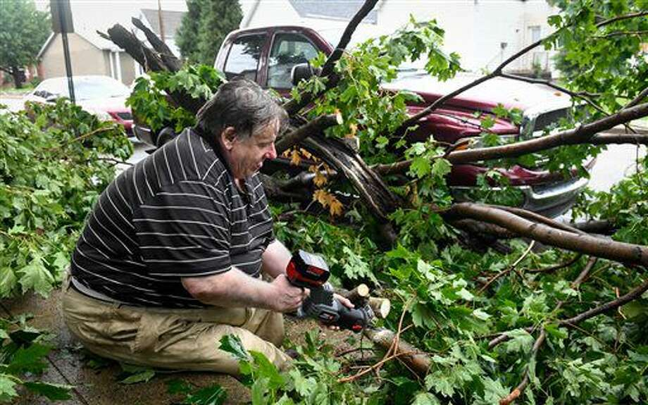 Dave French uses a battery powered saw to cut tree limbs that fell in his front yard and on his truck at 117 East Delaware Street after a severe storm moved through the Evansville, Ind. area Thursday afternoon, July 7, 2016. (Mike Lawrence/Evansville Courier & Press via AP) Photo: Mike Lawrence