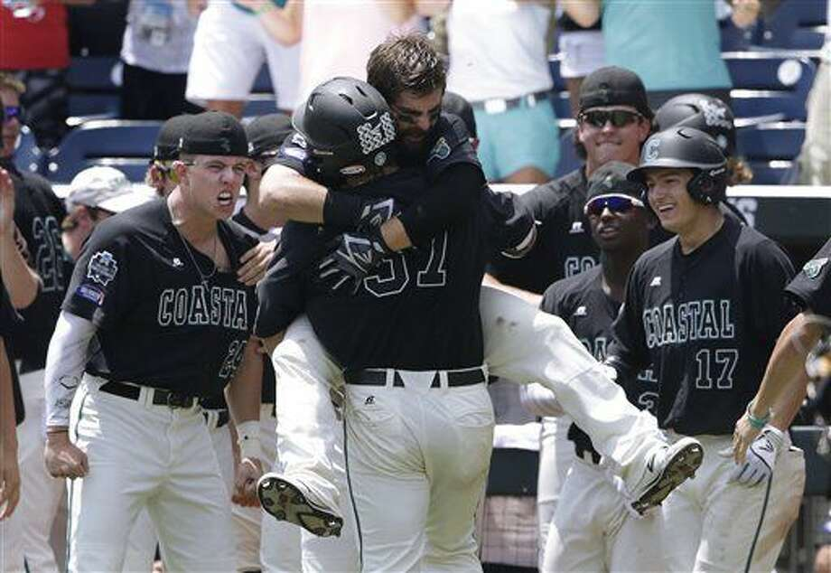 Coastal Carolina's G.K. Young (37) is hugged by Anthony Marks after hitting a two-run home run against Arizona in the sixth inning in Game 3 of the NCAA College World Series baseball finals in Omaha, Neb., Thursday, June 30, 2016. (AP Photo/Nati Harnik) Photo: Nati Harnik