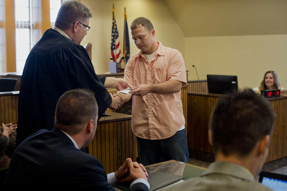 BRITTNEY LOHMILLER | blohmiller@mdn.net Midland County Circuit Court Judge Michael J. Beale, left, shakes hands with Charlie Overstreet concluding Overstreet's graduation from drug court on Thursday afternoon. Photo: Brittney Lohmiller/Midland Daily News