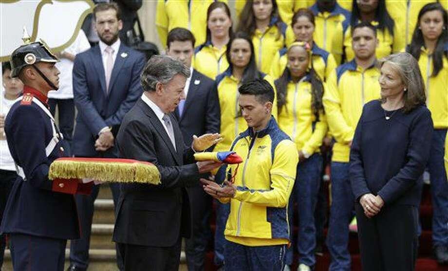 El presidente de Colombia, Juan Manuel Santos, entrega la bandera del país al gimnasta Josimar Calvo, durante una ceremonia realizada el jueves 7 de julio de 2016, en la que participaron los integrantes de la delegación que acudirá a los Juegos Olímpicos (AP Foto/Fernando Vergara) Photo: Fernando Vergara