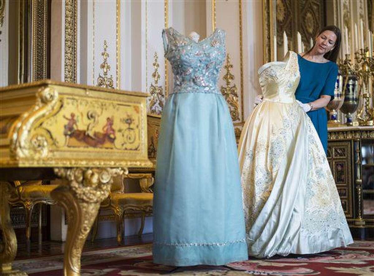 La curadora Caroline de Guitaut ajusta vestidos de la reina Isabel II durante una muestra previa a la inauguración de la exposición