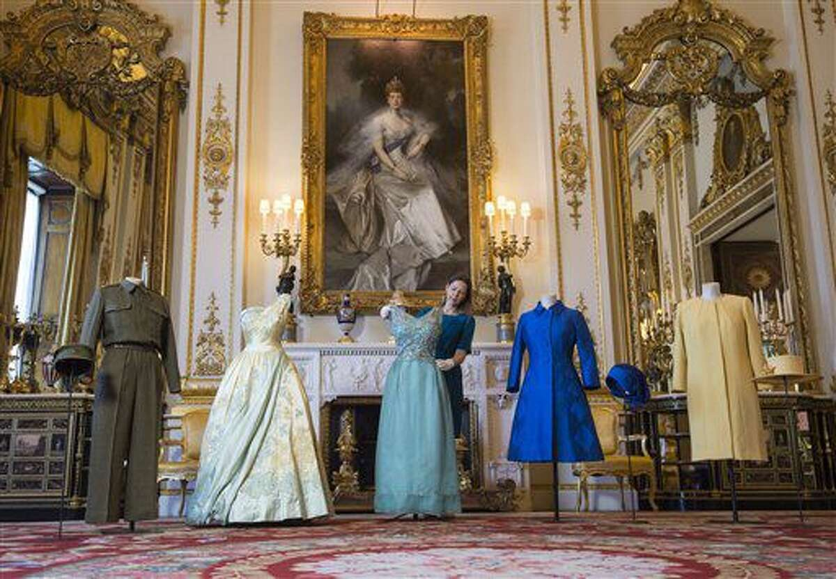 La curadora Caroline de Guitaut ajusta vestidos de la reina Isabel II durante un recorrido previo a la inauguración de la muestra